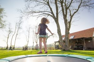 girl on backyard trampoline