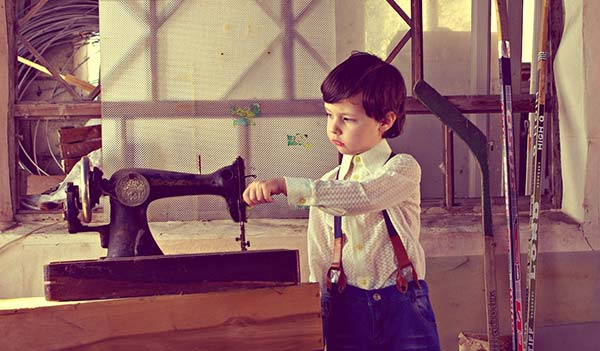 boy with vintage sewing machine